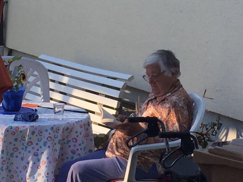 Una mujer lee en el patio de su vivienda
